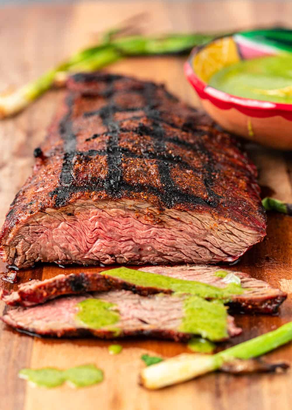close up shot of flap steak drizzled with chimichurri sauce