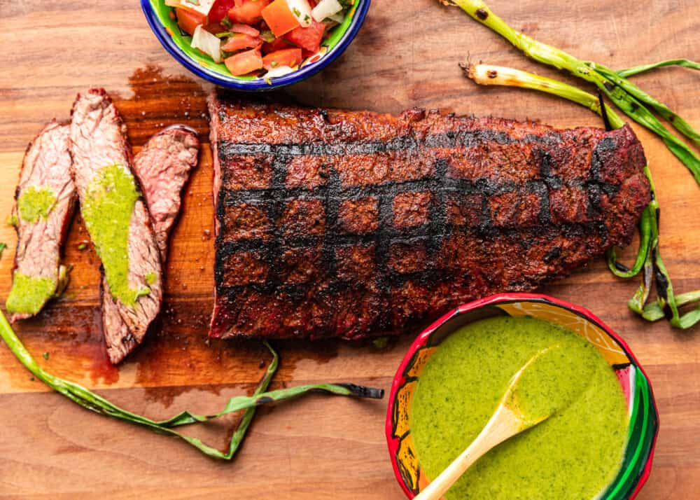 overhead image of grilled sirloin steak next to bowl of chimichurri sauce