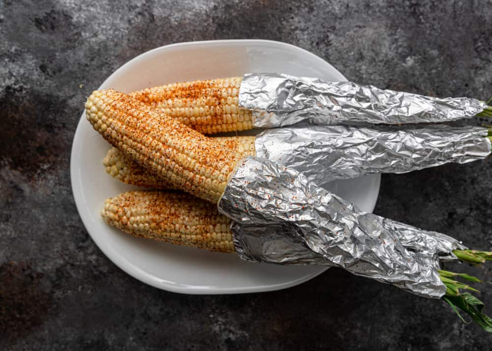 ears of corn wrapped in foil and seasoned for a street corn recipe