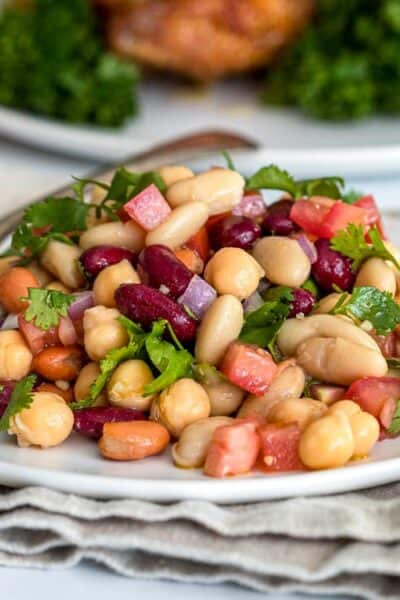 cold 4 bean salad with spicy vinaigrette on white plate