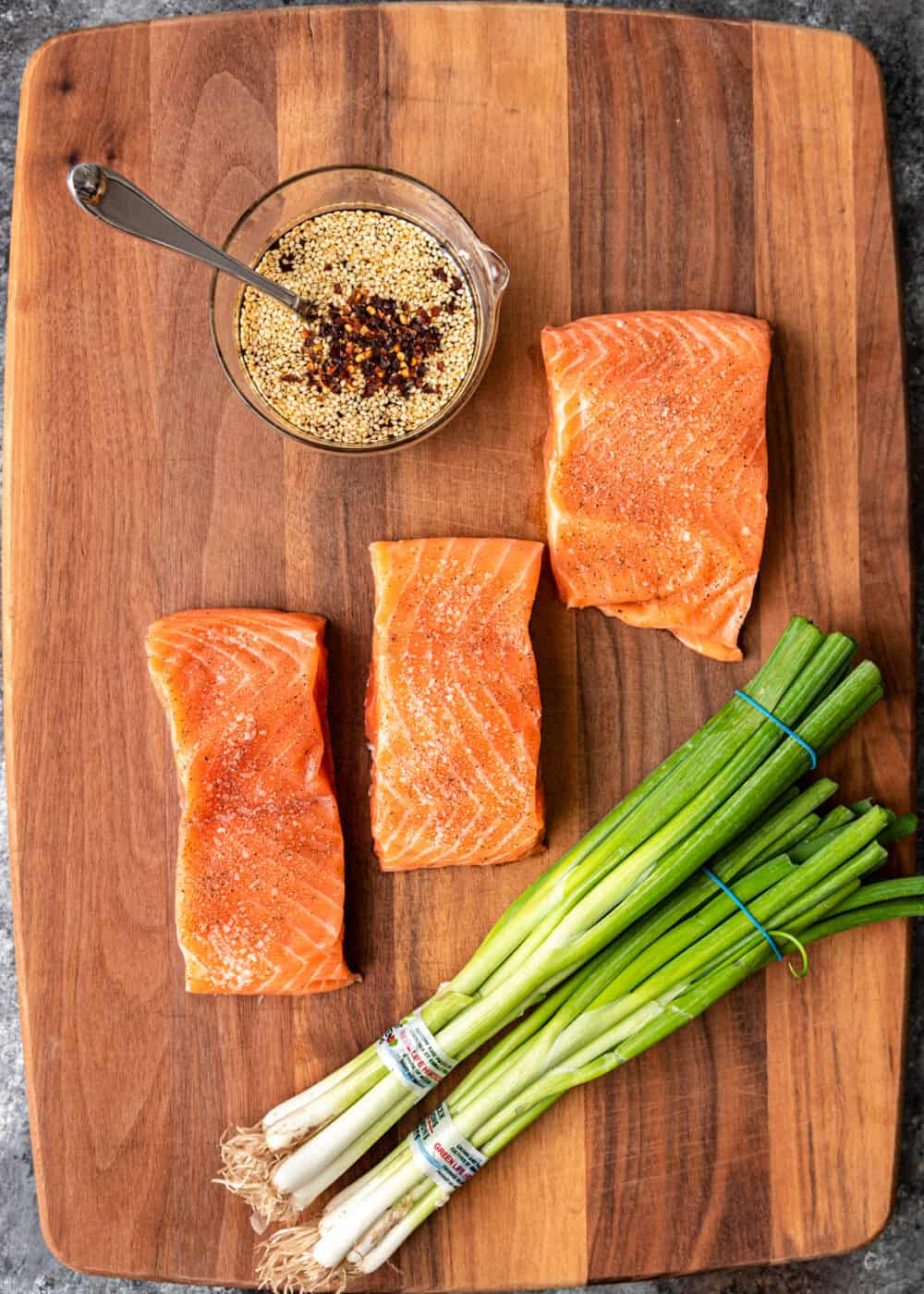 overhead image: 3 fish filets, scallions and seasoning to make a broiled salmon recipe