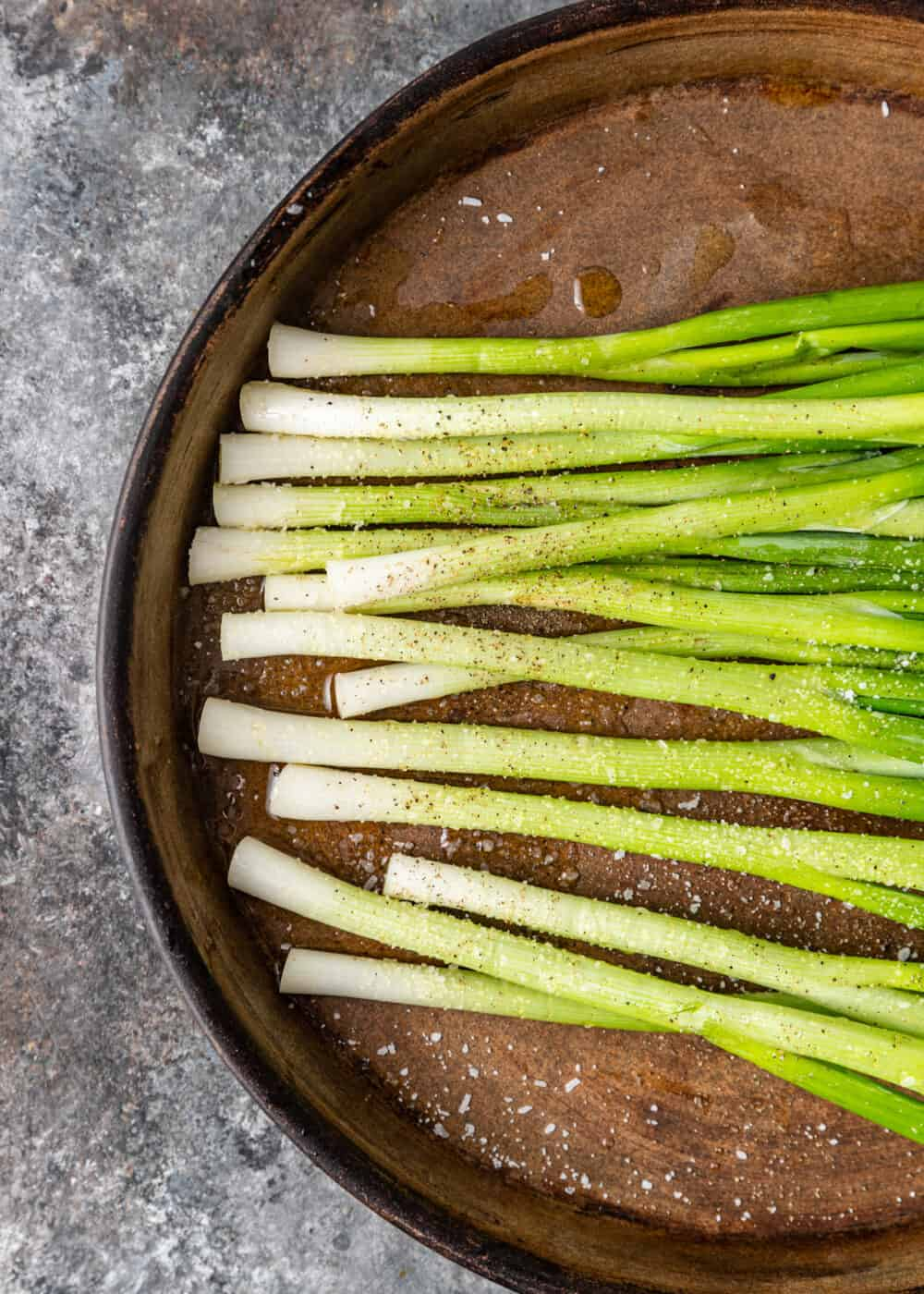 bunch of scallions sprinkled with seasoning on baking pan