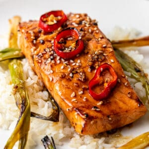 close up: salmon filet with garnish of sesame seeds and Fresno chile slices