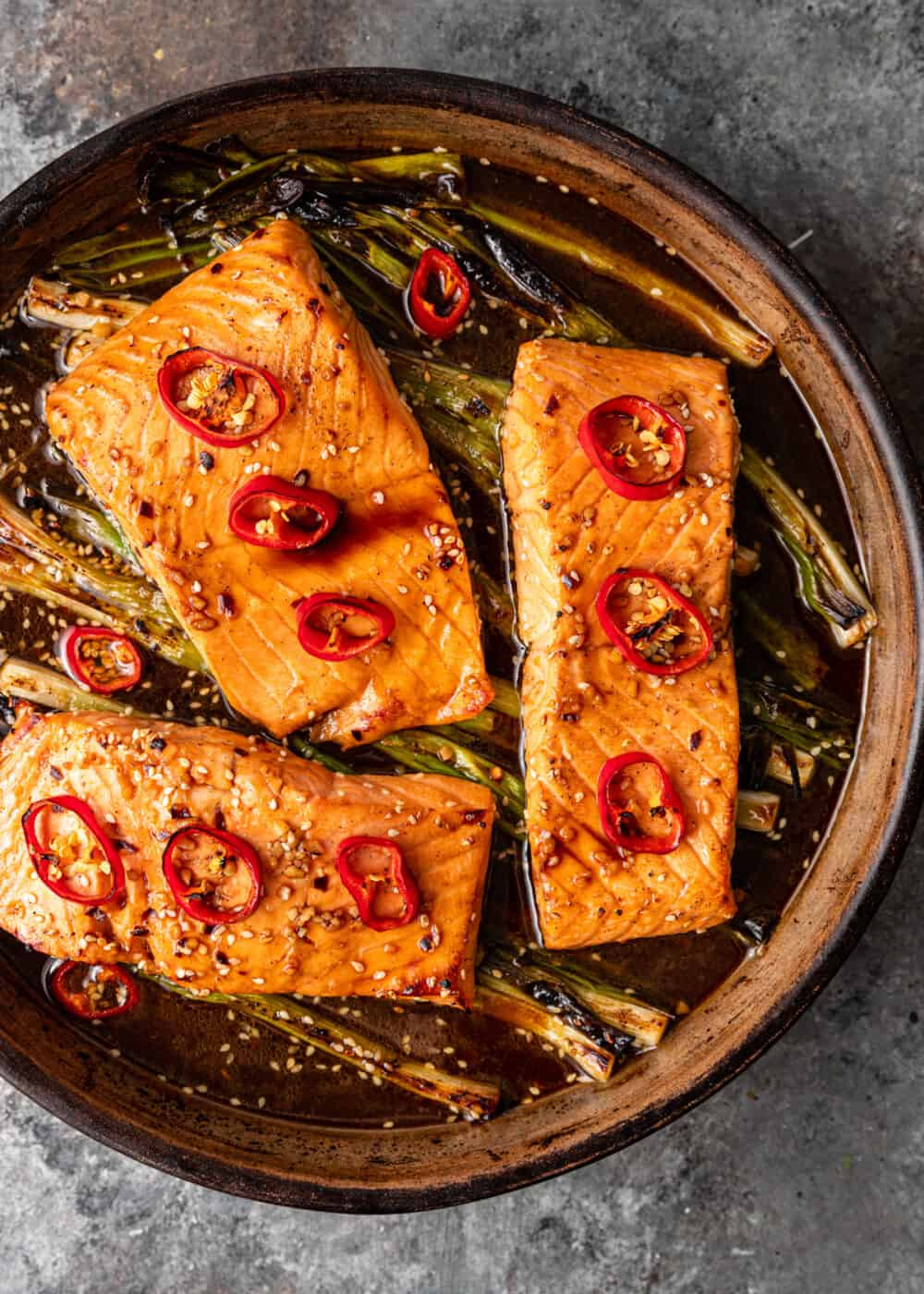 overhead image: round baking pan with three honey glazed salmon filets topped with slices of red chili peppers