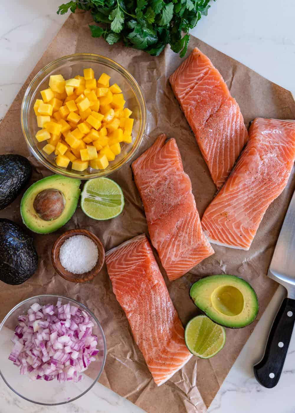 overhead image: 4 raw salmon filets, avocados cut in half, diced red onion and bowl of fresh mango cubes for grilled salmon recipe