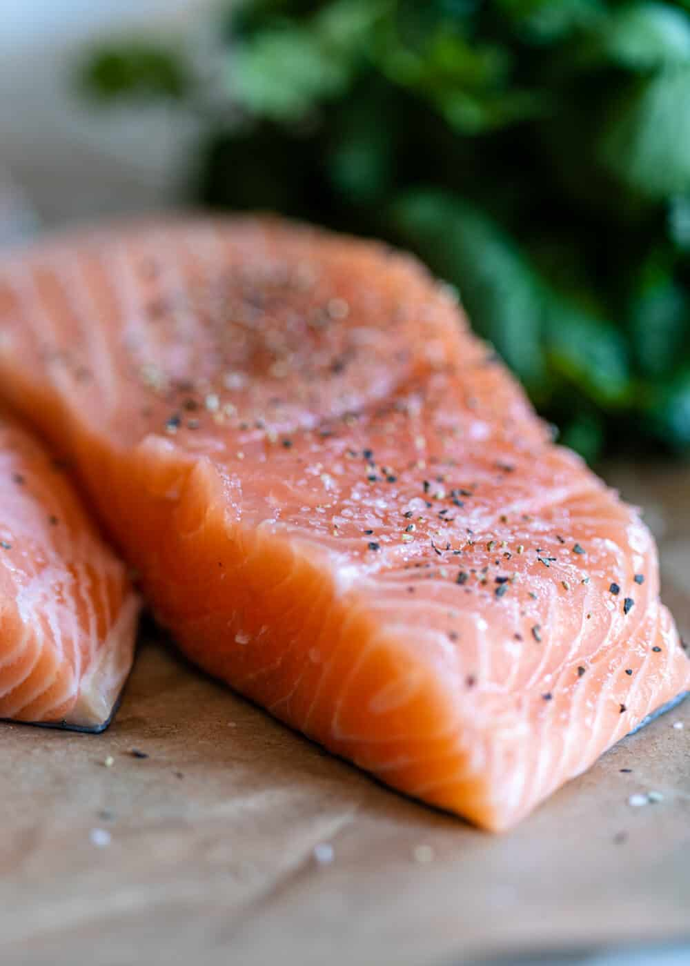 close up photo: raw salmon filet seasoned with salt and black pepper