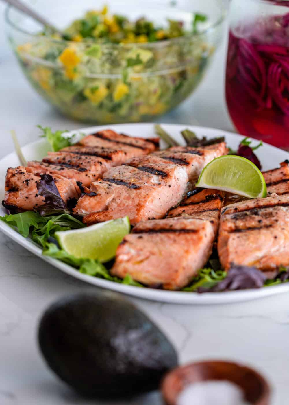 healthy grilled salmon filets on platter next to bowl of fruit salsa