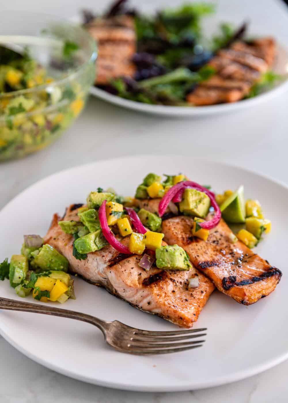 flaky fish topped with pieces of avocado, mango and pickled red onion