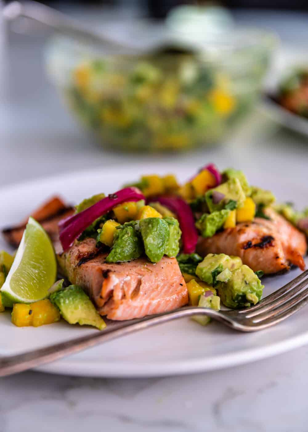 plate of healthy grilled fish filets topped with tropical fruit salsa