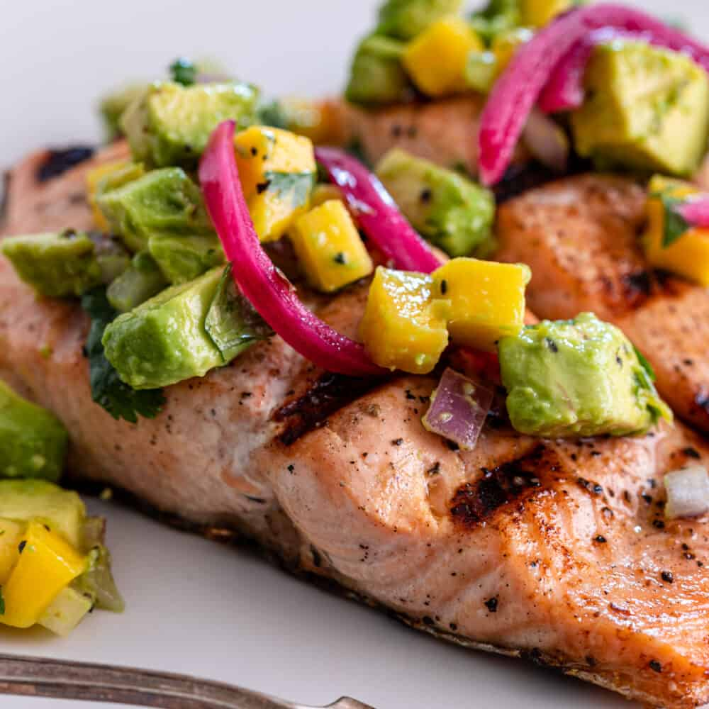 close up image of mango salsa on piece of cooked salmon
