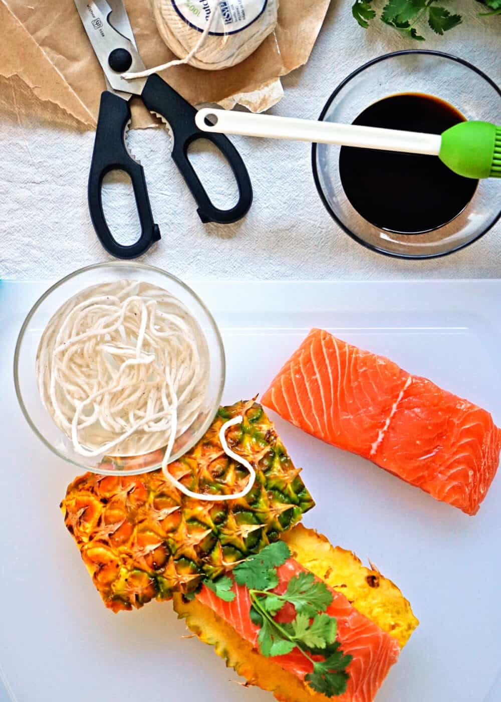 overhead image: counter top with raw salmon filet, bowl of teriyaki sauce, pineapple planks and cotton twine with scissors