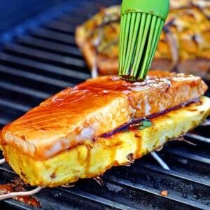 basting teriyaki sauce over salmon filet on a grill
