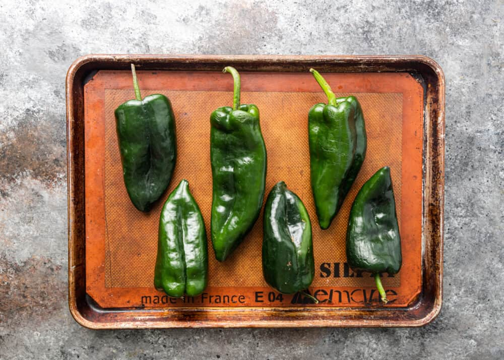 overhead image: six whole poblano peppers on sheet pan, ready for roasting