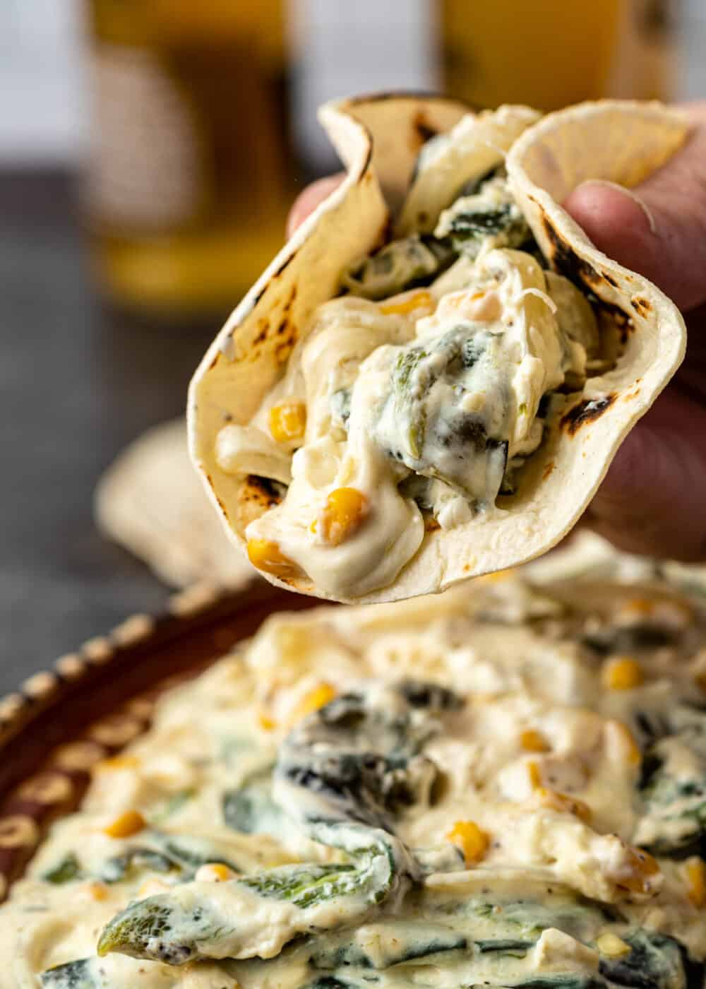 man's hand holding soft taco filled with slices of poblanos in cream sauce