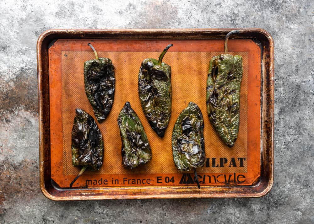 overhead image: roasted poblanos on baking sheet for making Mexican rajas con crema