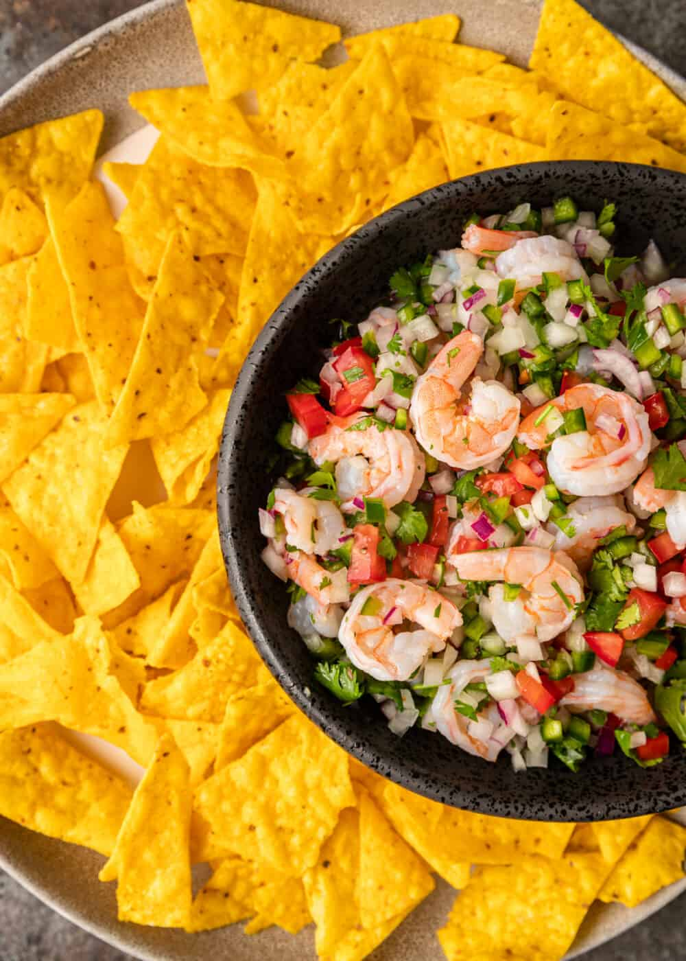 steeped shrimp ceviche in bowl with finely diced tomatoes and onions on platter with tortilla chips