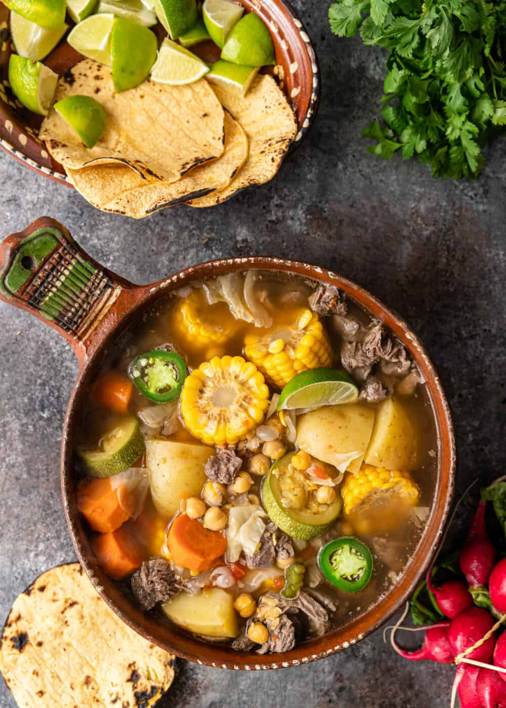 overhead: stoneware crock of caldo de res soup next to basket of tortilla chips and lime wedges