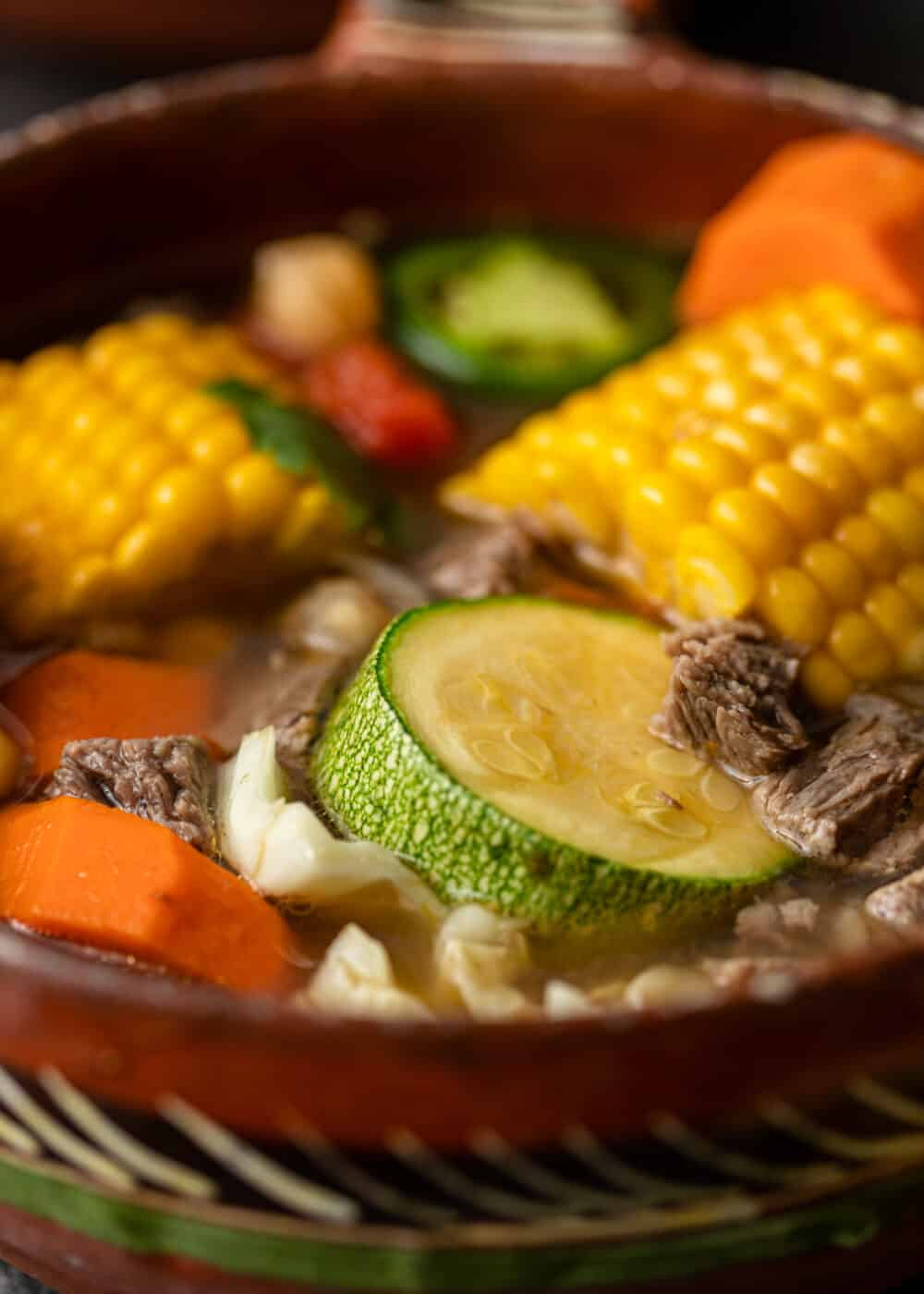close up: bowl with beef broth, small pieces of beef and slices of carrots and zucchini