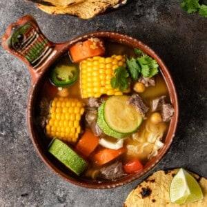 overhead image: bowl of caldo de res (vegetable beef soup)