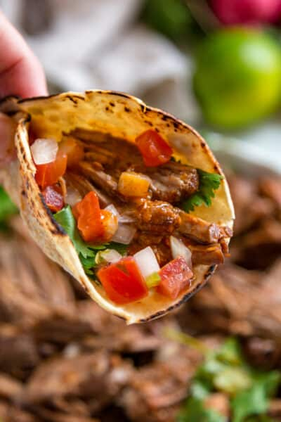 instant pot barbacoa inside corn tortilla with taco toppings