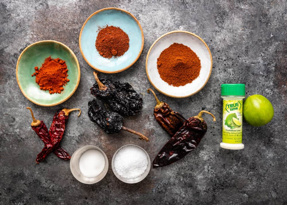 3 small bowls of ground Mexican spices next to dried guajillo chiles, ancho chiles, and California chiles