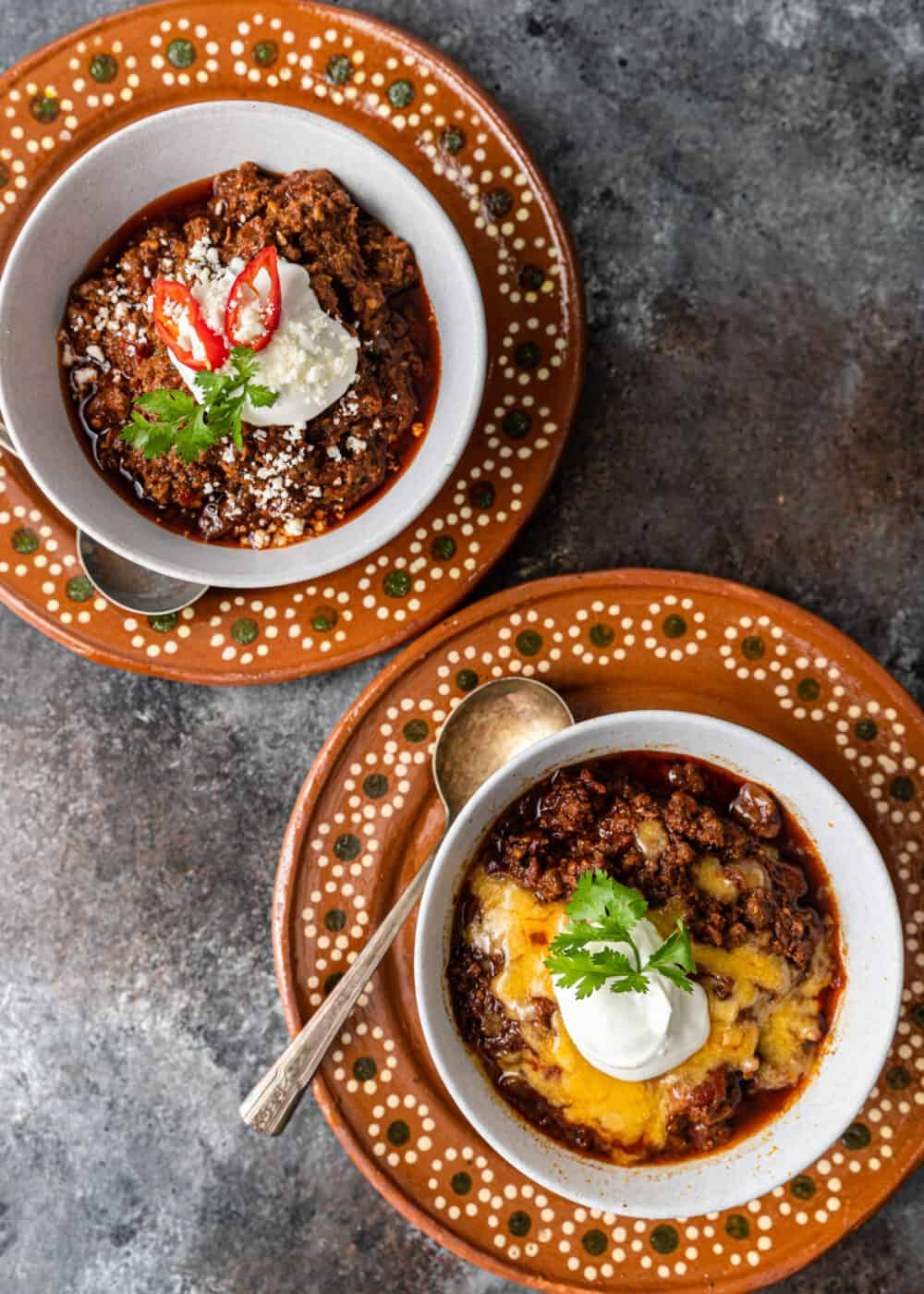 overhead: 2 bowls of five alarm chili side by side on glazed pottery plates