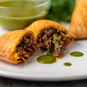 beef empanada cut in half, juicy beef verde sauce