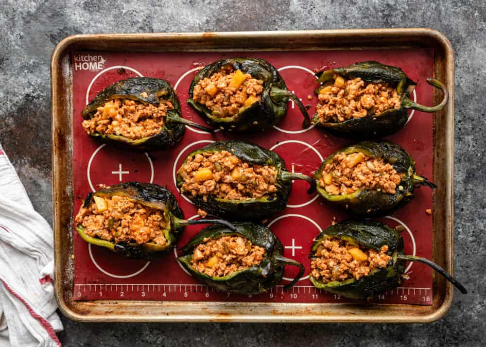 overhead: chicken stuffed poblano peppers on baking sheet