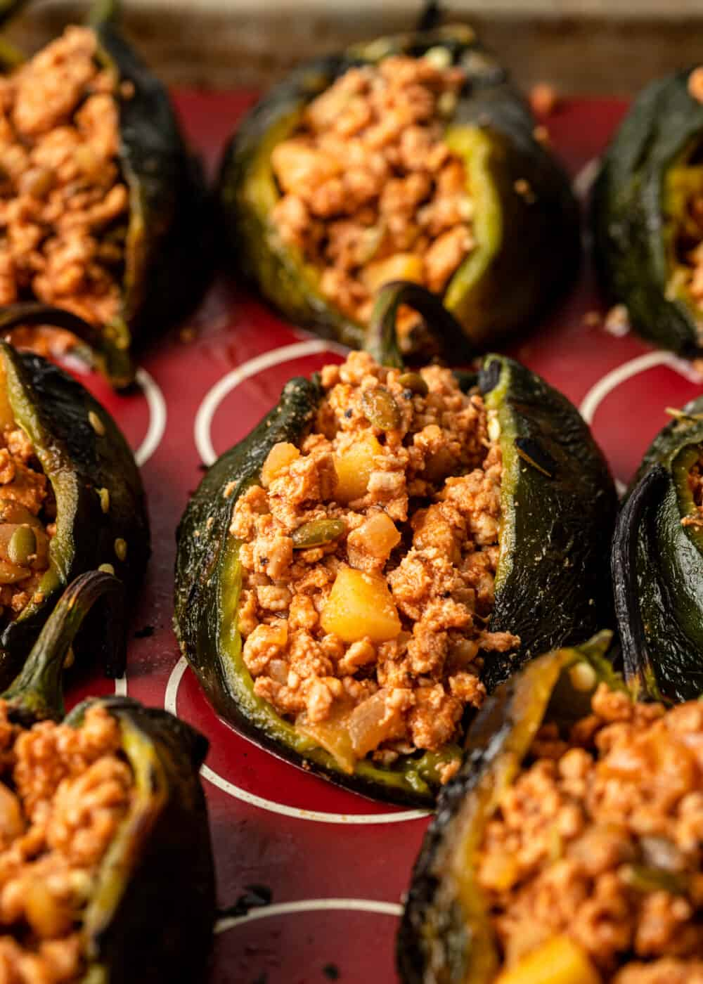 poblano chiles on baking sheet stuffed with ground meat