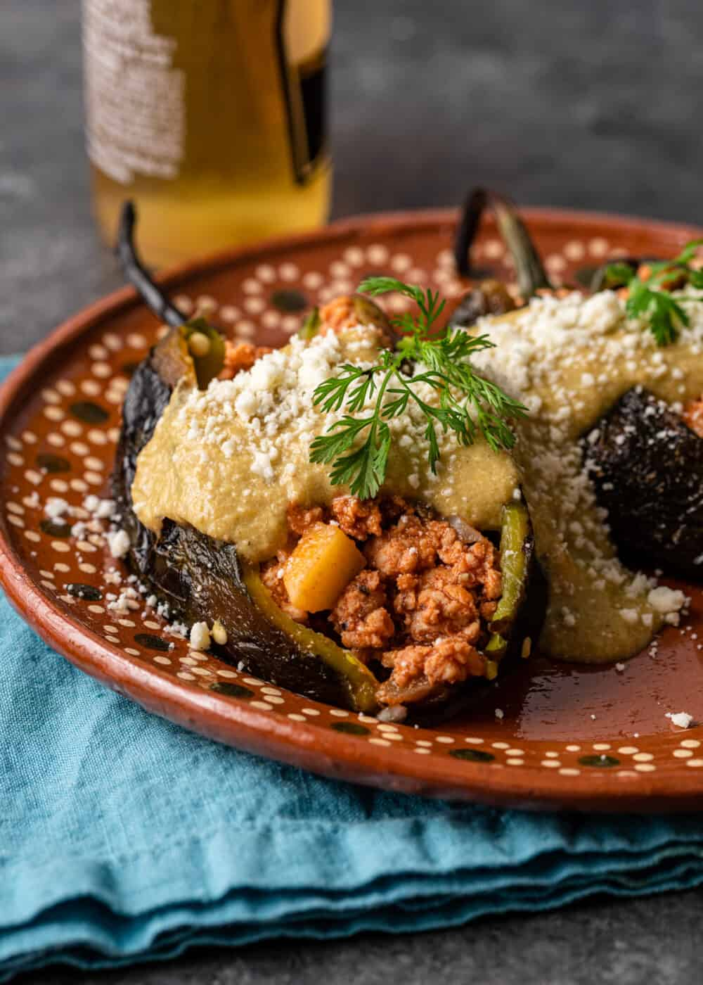 plate of chicken stuffed poblano peppers covered in creamy green sauce