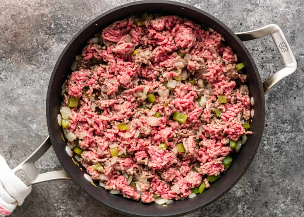 overhead: raw ground beef cooking in skillet with onions and bell peppers