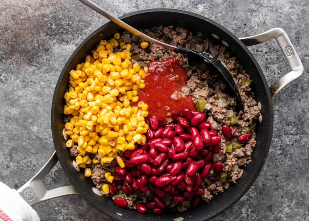 overhead: combining ingredients in skillet for ground beef tamale casserole