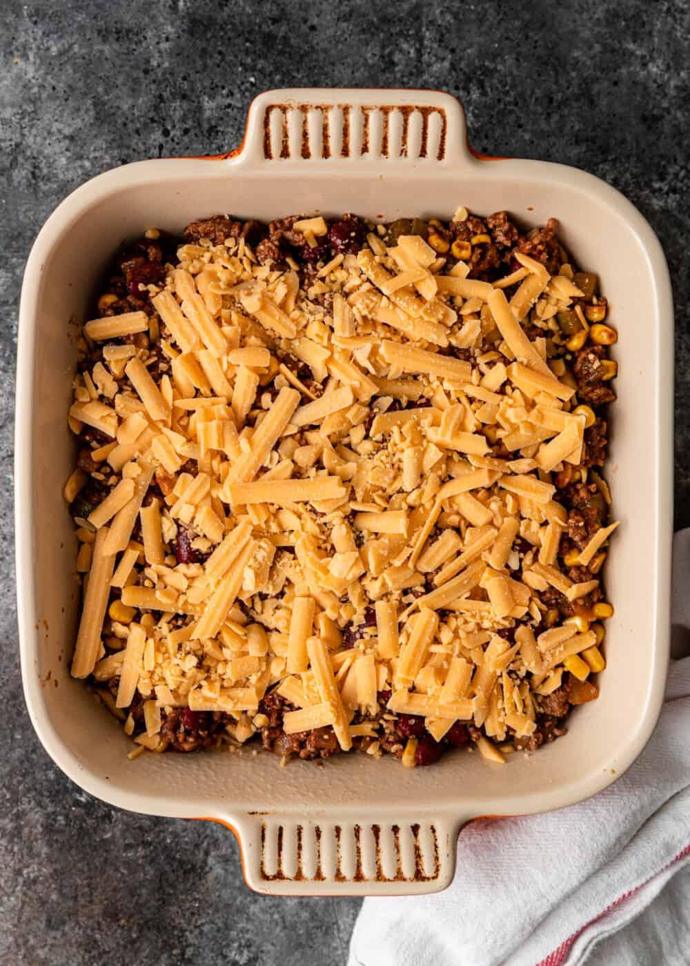 overhead: shredded cheddar cheese over tex mex chili in casserole dish