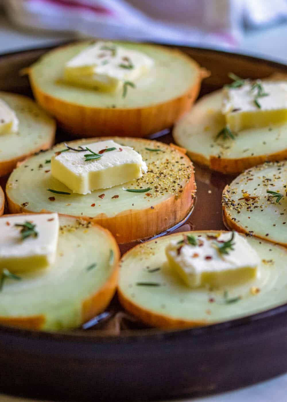 close up: raw vegetable slices in baking dish- pats of butter on top