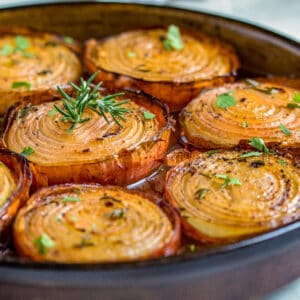 close up of baked onion halves with rosemary