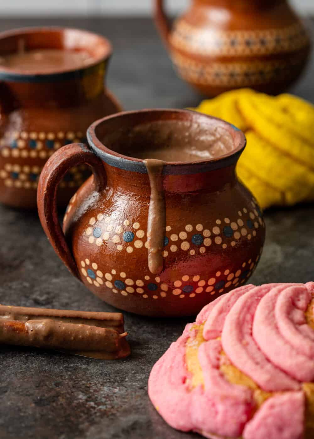 3 mugs of hot champurrado - front mug with chocolate dripping over edge