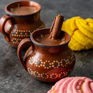 2 glazed pottery mugs filled with dark chocolate drink