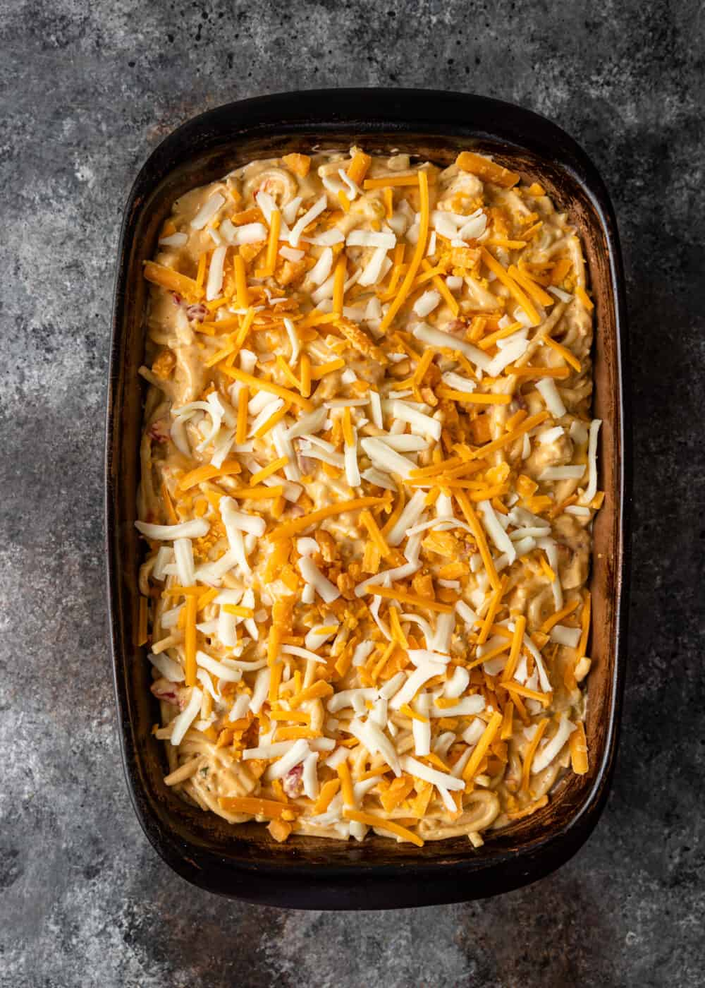 shredded white and yellow cheeses on top of casserole