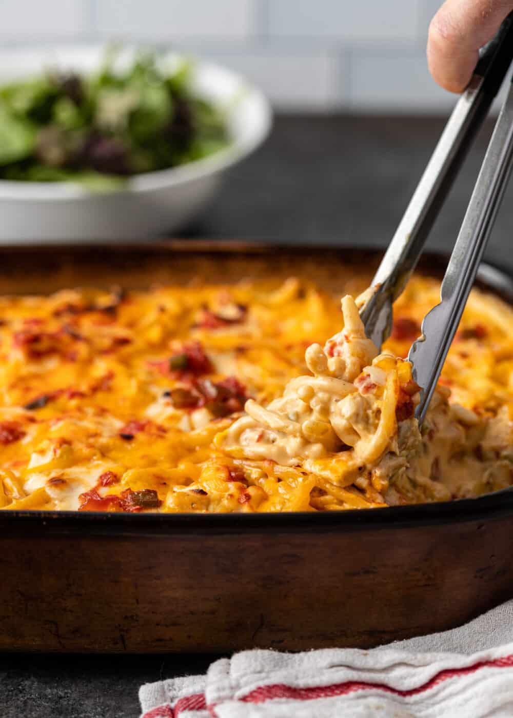 using tongs to serve chicken spaghetti casserole